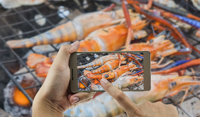 Man is using mobile phone taking photo of grilled shrimp over hot charcoal