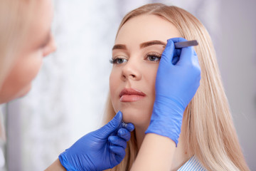 Professional using forceps for plucking eyebrows.