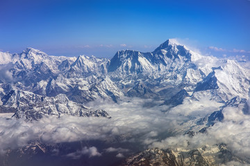 Himalaya mountains Everest and Lhotse, with snow flags and clouds, view from plane
