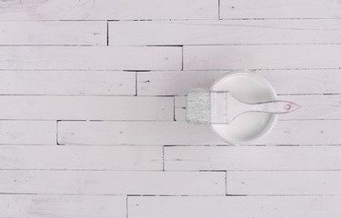 Bank of white paint, paint brush on a white wooden surface