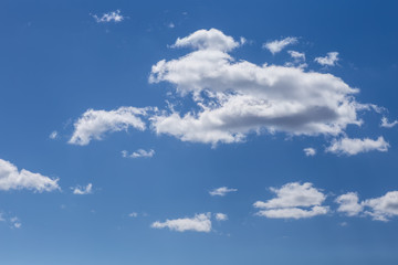 the clouds drifting across the blue sky