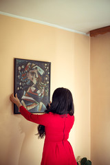 Woman in red hanging art picture on wall