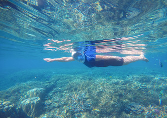 Woman swims undersea in swimming costume and full-face mask.