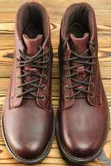 Stylish brown leather boots for men on wooden background.