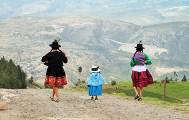 Traditional Peruvian woman with child in Ayacucho Peru walking in highlands of the Andes mountains