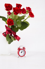 Bouquet of red roses with red alarm clock on white background