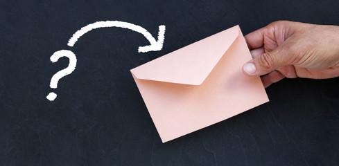 Enveloppe et un point d'interrogation à la craie sur ardoise