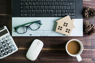 Top view of office stuff with laptop wireless mouse calculator coffee cup and wooden house toy on wooden table.Concept workplace.Real estate concept, New house concept, Finance loan business concept.