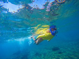 Woman in snorkeling mask underwater photo. Female snorkel above sea bottom and corals.