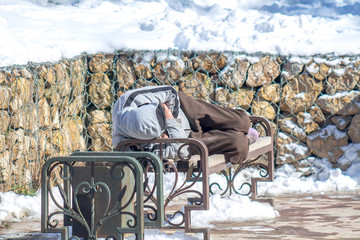 homeless sleeps on a bench in the park in winter