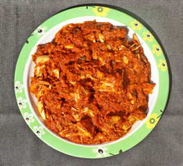 Kathal ki Masaledar Sabzi (spicy jackfruit curry) in a plate on black background.