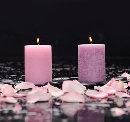rose petals with two white candle and therapy stones
