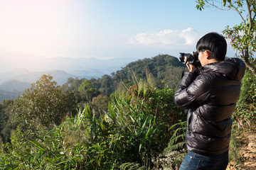 Young professional traveler man with camera shooting outdoor, fantastic mountain landscape.