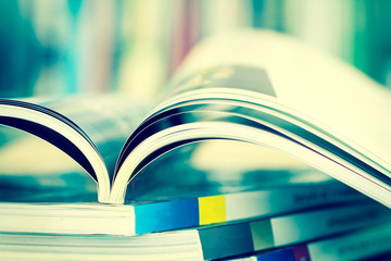 Close up opened magazine page with  blurry bookshelf background for bublication concept , extremely DOF with vintage retro color tone