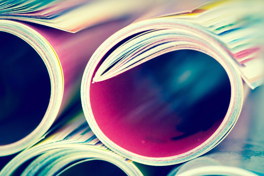 Close up edge of colorful magazine stacking roll with  blurry bookshelf background for bublication and publishing concept , extremely DOF with vintage retro color tone