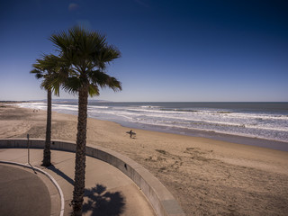 Surfer walking on Pismo Beach in California