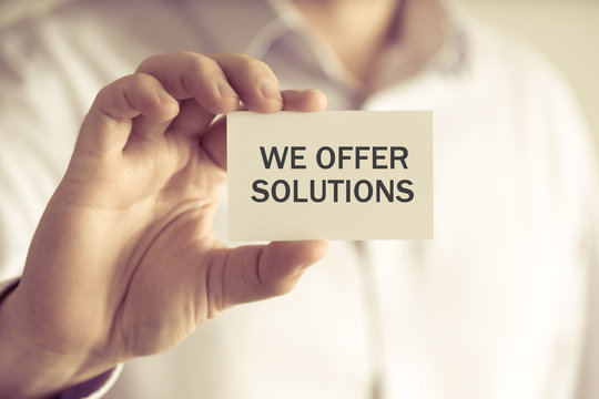 Businessman holding WE OFFER SOLUTIONS message card