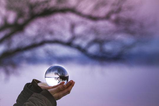 Glaskugel in den Händen einer Frau am Flußufer