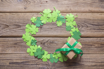 Round frame of clover leaves and gift box on the old wooden boards. St.Patrick's day background. Space for text.