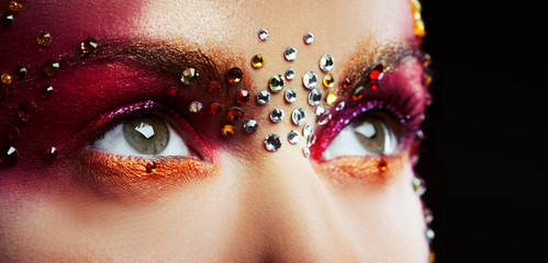 Eyes of a beautiful young woman in a bright designer makeup with rhinestones