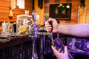 Close-up of bartenders hands pouring beer