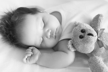 Adorable baby, peacefully asleep in crib next to a teddy bear on a cool afternoon in black and white.