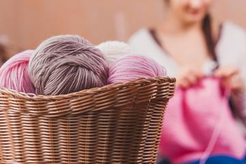 The woman knits woolen clothes. Knitting needles. Close-up. natural wool