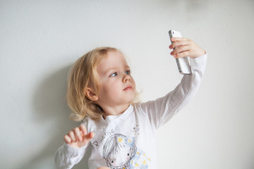 beautiful little girl with a smartphone makes selfie