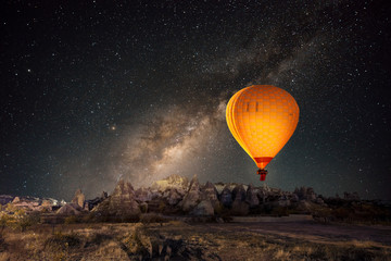 Hot air balloon flying over spectacular Cappadocia under the sky with milky way and shininng star at night