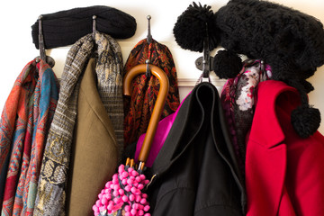 Colorful clothing, coats, hats and umbrella on coat hook – cold winter season