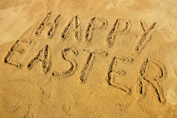 Message Happy Easter handwritten on the golden sandy beach