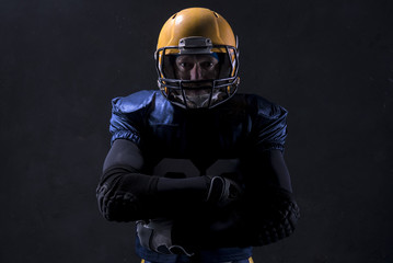 Portrait of Caucasian male american football player standing against dark background
