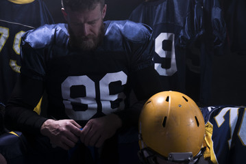 Portrait of Caucasian male American football player preparing for a game in a locker room