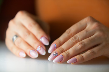 female pink French manicure on beautiful background