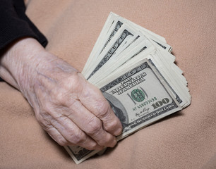 Old woman's hands holding dollars