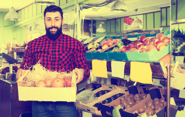 Male shop assistant demonstrating pomegranates