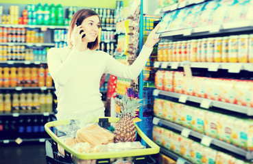 Young female talking on phone about shopping