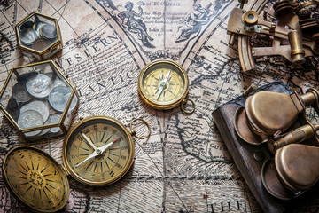 Compass, sextant and old coins on vintage map. Retro style.
