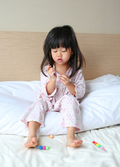 Little child girl play and learn magic color on the bed at the morning.