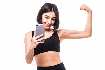 Happy sporty woman making selfie photo on smartphone and showing biceps