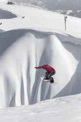 Jumping snowboarder in winter mountain. Extreme sport.
