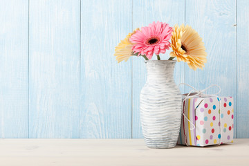 Fresh colorful gerbera flowers and gift box
