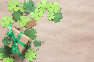 Gift box with paper clover leaves on the brown paper. St.Patrick's day  background. Space for text.