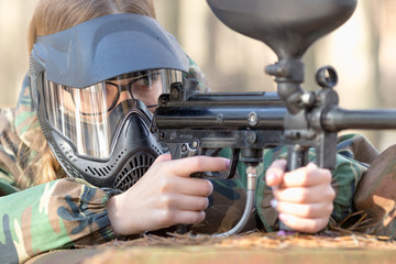 girl playing paintball in overalls with a gun.
