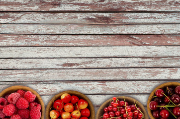 Red berries at border of image with copy space for text. Raspberry, strawberry, pomegranate, currant in a wooden bowls. Top view.