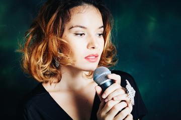Studio portrait of woman singer with microphone in dark green background