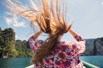 Portrait of beautiful girl traveling by boat in mountain tropical lake, the wind fluttering hair. Summer Travel concept, Thailand, Cheow lan lake
