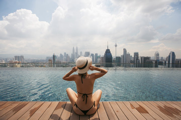 Woman in white hat sitting at Swimming pool on roof top with beautiful city view kuala lumpur Malaysia