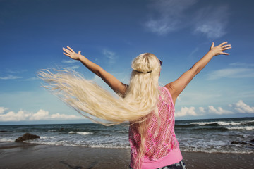 Freedom woman in free happiness bliss on beach. Happy female blond model enjoying serene ocean nature during travel holidays vacation outdoor