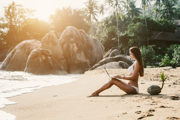Woman sitting on sea shore working with laptop computer on tropical island beach under palm tree